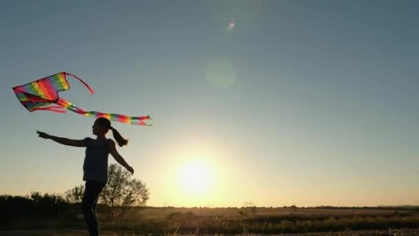 junges Mädchen spielt bei Sonnenuntergang mit einem Drachen