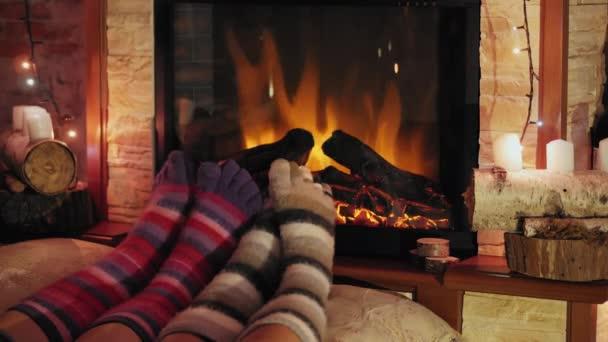 Nohy z vlněné ponožky hořící vánoční útulného krbu. 4 k. pár uvolňuje teplo u krbu a zahřívání nohou. Zimní a vánoční svátky koncept.