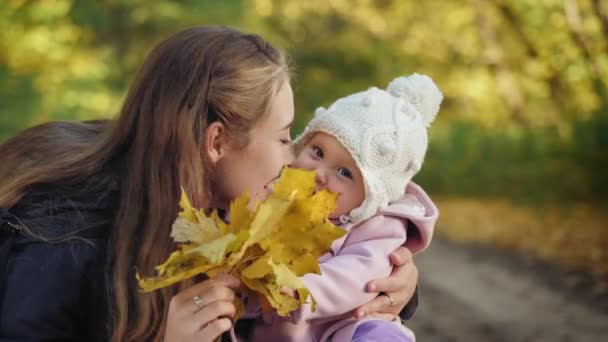Baby girl with mother smiling in the autumn park