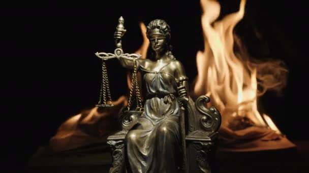 Statue of Lady Justice on the background of the flame of a burning book