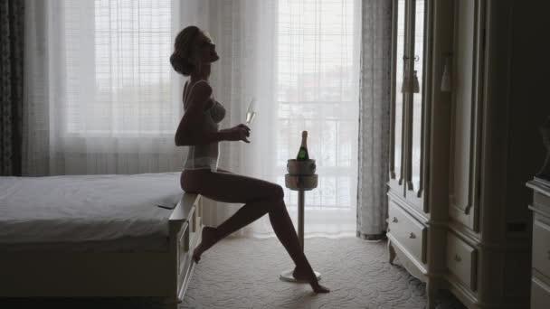 Dívka se těší šampaňské. Silueta nahé dívky
