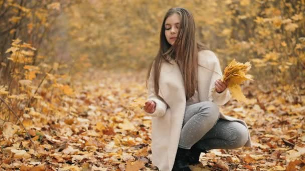 Cute teen girl collects a bouquet of autumn leaves
