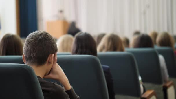 Rückansicht eines gelangweilten Zuhörers, der im Saal sitzt und dem Redner zuhört