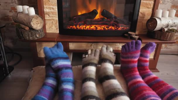 Feet in woolen funny socks warming by cozy fire in Christmas time