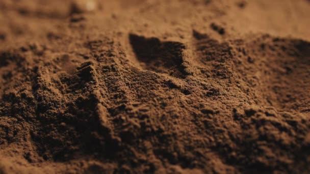 Runde Kekse mit einer Herzform in der Mitte fallen in Kakaopulver