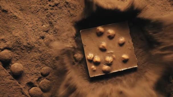 Schokoriegel mit Nüssen, die in Kakaopulver fallen