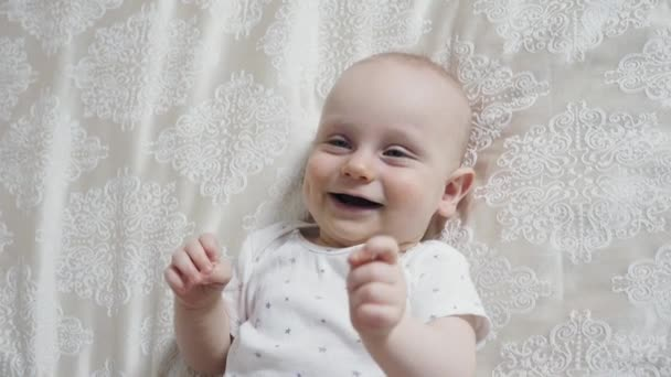 glücklicher neugeborener Junge liegt auf ihrem Rücken und lächelt