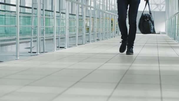 ein junger Mann mit Handtasche in einem modernen Flughafenterminal