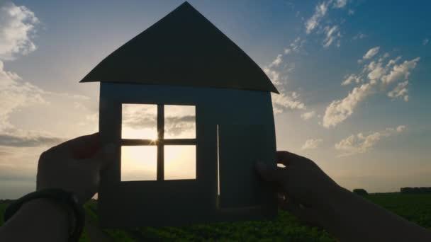 Sen o vlastním domě. Uzavření rukou, které drží papírový model doma na poli při západu slunce. Silueta papírového domku v paprscích zapadajícího slunce