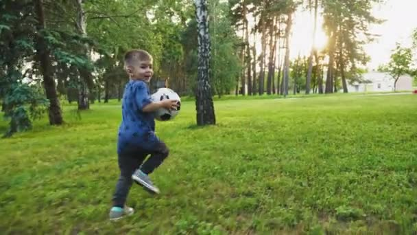 A cute little boy holding a soccer ball, running away over green grass and smiling happily. Slow motion shot