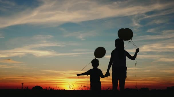Silhouette two children with balloons at sunset
