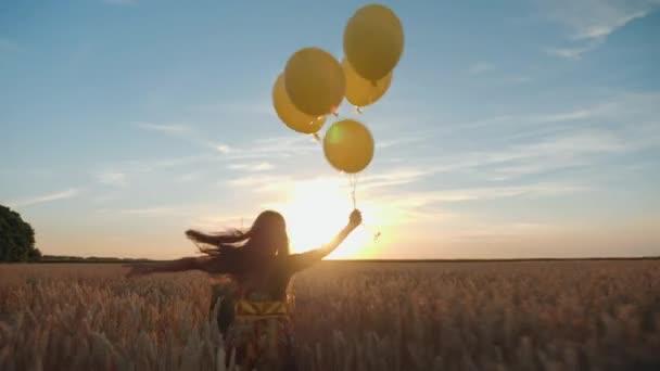 junges Mädchen mit Luftballons auf dem Feld