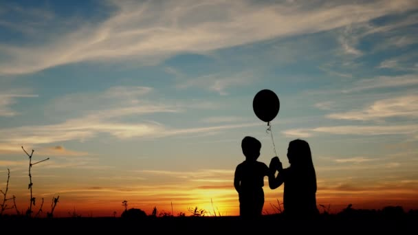 Silhouette two children with balloon at sunset