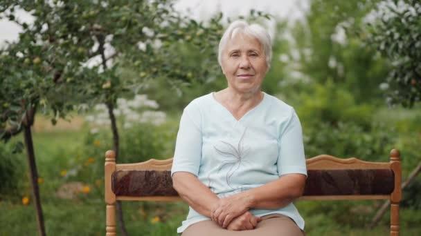 Donna anziana seduta su una panchina in giardino