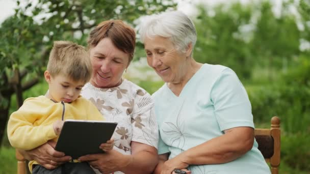 Grandmothers look at a tablet in the hands of a grandson