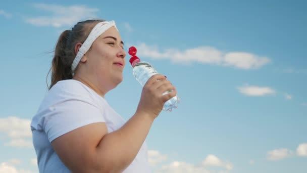 Fat girl drinks water from a bottle