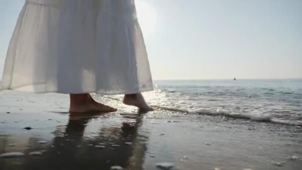 Female legs touching sea water, slow-motion