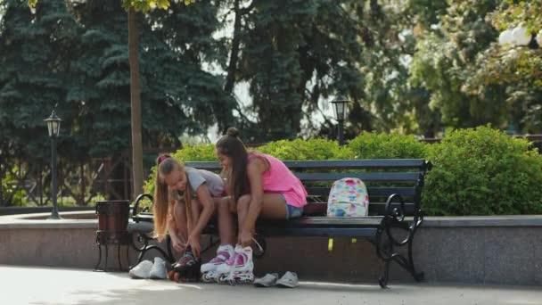 Mladé dívky sedící na lavičce na kolečkových brusle