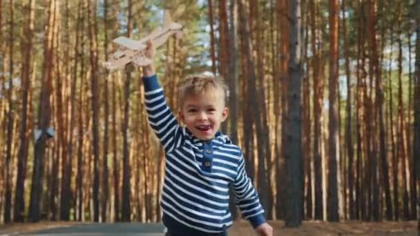 glücklicher kleiner Junge, der mit einem Spielzeug-Holzflugzeug spielt