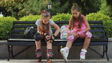 Young teen girls preparing for roller-skating