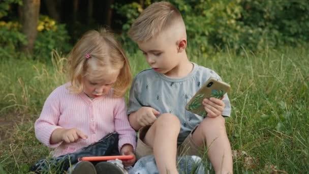 Děti si hrají s chytrými telefony v parku