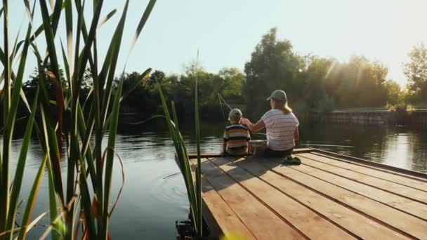 Mutter und kleiner Sohn angeln am See