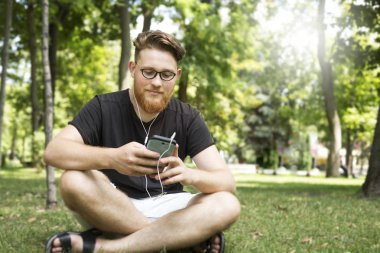 Cute bearded redhead young man in headphones listening to music on a smartphone while sitting in a park. The guy with glasses and a stylish haircut uses a mobile phone.