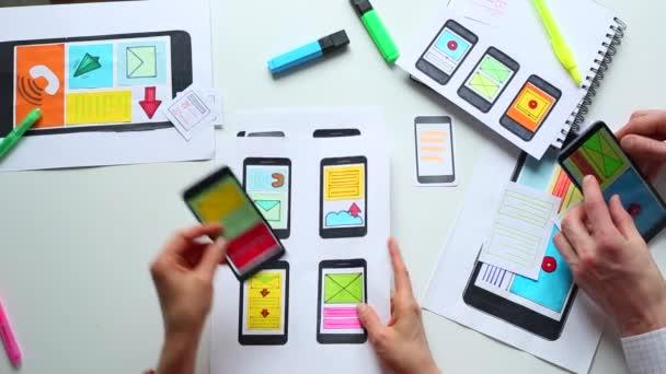 Egy csapat webtervező fejleszt interfész alkalmazásokat mobiltelefonokhoz az asztali számítógépen. A művészek okostelefonokat rajzolnak. Első látásra. Találkozó üzletemberekkel.