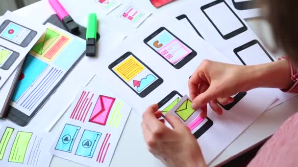 Webový designér pracuje na rozhraní pro aplikace mobilních telefonů. Vývojář kreslí náčrty uživatelských aplikací pro chytré telefony.