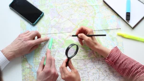Mladí lidé plánují dovolenou podle mapy světa. Cestovní koncept.