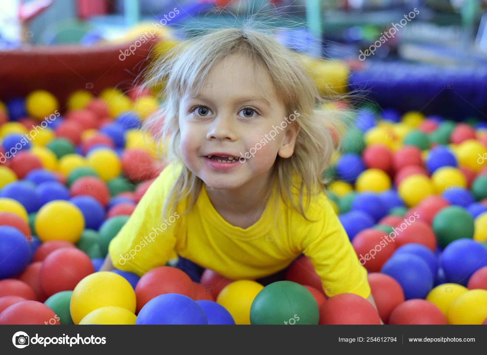be43bcce3 Retrato de un niño rubio en una camiseta amarilla. El niño sonríe y juega  en la ludoteca. Piscina de bolas. — Foto de Ninulia0820
