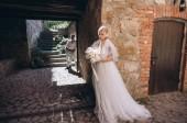 atraktivní mladá nevěsta a ženich pózuje ve starém městě