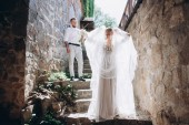 Fotografie beautiful bride and handsome groom on stairs of ancient building in old town