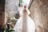Fotografie beautiful bride and groom on stairs of ancient building in old town