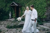bride and groom walking in front of ancient building covered with vine and green leaves