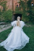 rear view of young bride in beautiful wedding dress in front of ancient building covered with vine