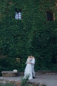 beautiful bride and groom embracing in front of building covered with vine and green leaves