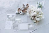 top view of stylish wedding invitations with bridal shoes and bouquet on wooden floor