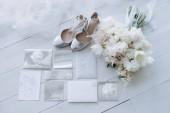 pohled shora na stylové svatební pozvánky svatební boty a kytice na dřevěnou podlahu