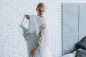 krásná mladá nevěsta s svatební šaty na závěs doma
