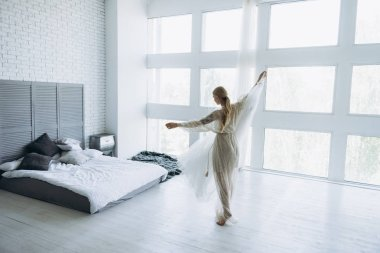 beautiful young bride with dress on hanger in bedroom