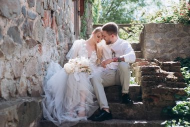 bride and groom sitting on stairs at old town