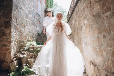 beautiful bride and groom on stairs of ancient building in old town