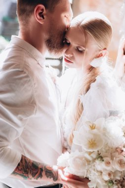 close-up portrait of beautiful young cuddling bride and groom