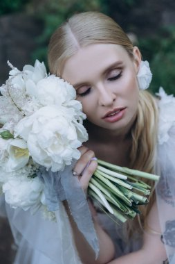 close-up portrait of beautiful young bride in dress with bouquet