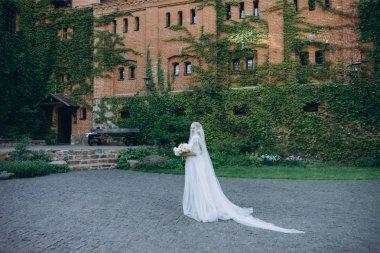 attractive young bride in garden in front of ancient building
