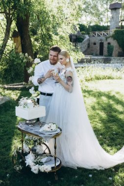 bride and groom with champagne glasses and cake on stand
