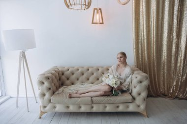 sensual young woman sitting on couch with bouquet