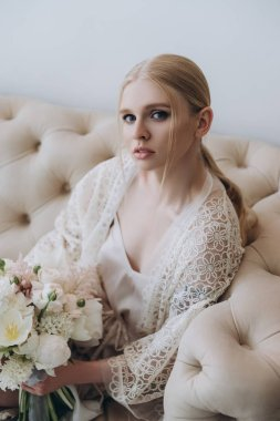 attractive young woman sitting on couch with bouquet looking at camera