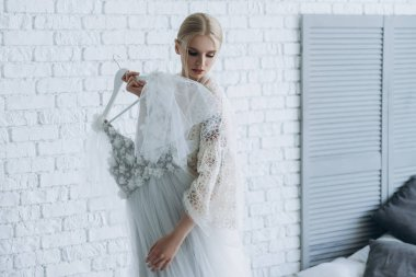 beautiful young bride with wedding dress on hanger at home
